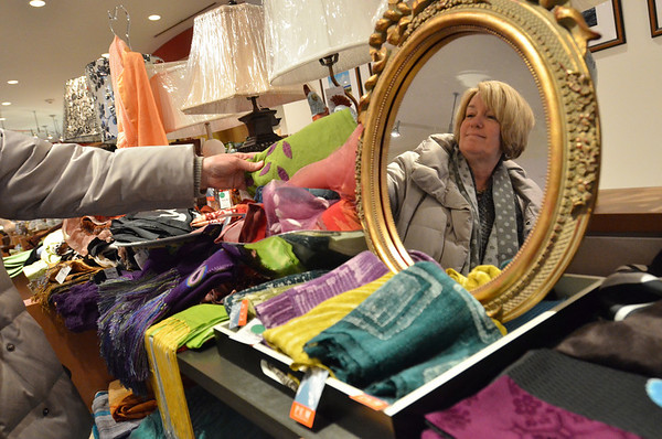 Salem: Mary Colpoys of Watertown peruses textiles from all over the world at the Peabody Essex Museum gift shop.  photo by Mark Teiwes  / Salem News