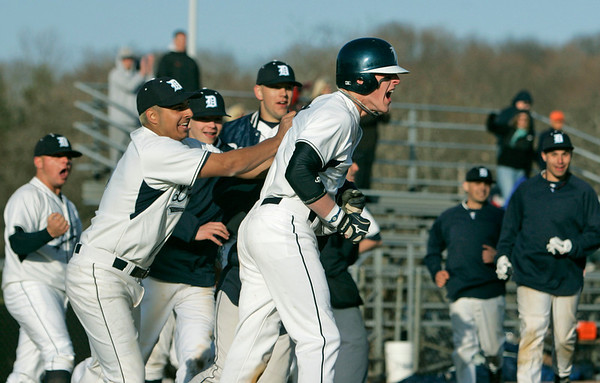 Danvers: Danvers' captain Greg Little, right, celebrates with his team after scoring the winning run in the team's 2-1 win over Swampcott.  photo by Mark Teiwes / Salem News