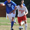 Topsfield: Masconomet's Chad Burke, right, dribbles upfield with Danvers defender Brian O'Keefe closely behind.  photo by Mark Teiwes / Salem News