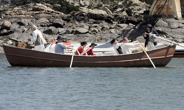 Marblehead: A boat of historical re-enactors approach a mock battle scene at Gas House Beach. photo by Mark Teiwes / Salem News