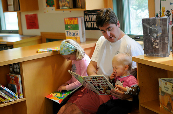 Hamilton: Bob McGinness of Hamilton spends a Saturday morning reading at the library with his daughters Charlotte, 6, and Sophie, 18 months.  photo by Mark Teiwes / Salem News