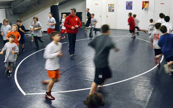 Danvers: The wrestlers run laps around the training room.    photo by Mark Teiwes / Salem News