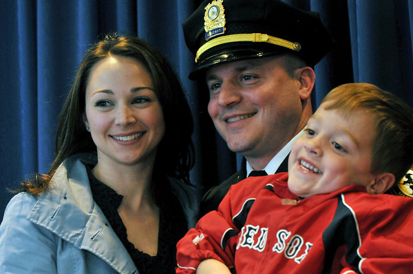 Salem:  Kristian Hanson, center, stands with his wife Susan and son Owen, 3, after being honored with three other officers for their part in recent high-profile arrest of a armed robbery suspect.  photo by Mark Teiwes / Salem News