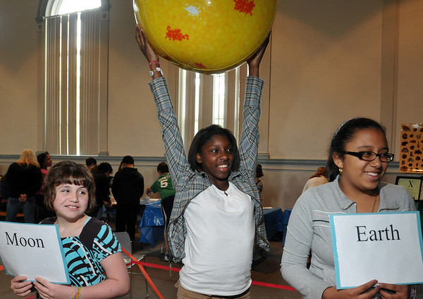 Salem: Saltonstall School students Joelle L'Heureaux, left, Saira Zapata, and Tahisha Reynoso get hands on practice acting out the orbits of the sun moon and earth during a special science, technology and engineering MCAS review session. photo by Mark Teiwes / Salem News