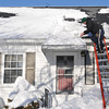 Beverly:  Justin Gadd of Cicoria Tree and Crane Service clears a ice dam from a client's house using a chisel, shovel, hammer, and ladder.  photo by Mark Teiwes  / Salem News