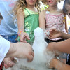 Salem: MiClaire Perez, left, and Blake Walton learn about gasses during an experiment with dry ice and detergent at the annual Read Buffam Science and Family Picnic.   photo by Mark Teiwes / Salem News
