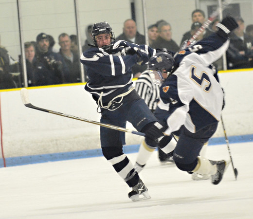 Malden: St. John's Prep captain Colin Blackwell checks Malden Catholic player's Mike Iovanna to the ice.  photo by Mark Teiwes  / Salem News