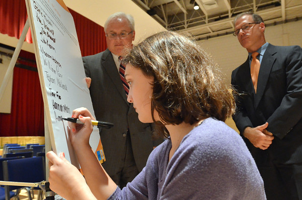 Salem: District Attorney Jonathan Blodgett and State Representative John Keenan, right, watch as Amanda Mazola, a Salem High School junior class officer, signs a pledge not to send text messages while driving.      photo by Mark Teiwes / Salem News
