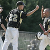 Peabody: Bishop Fenwick's Joseph Lavasseur, left, and Brian Sullivan high five David Ruggiero after he scored a run. photo by Mark Teiwes / Salem News