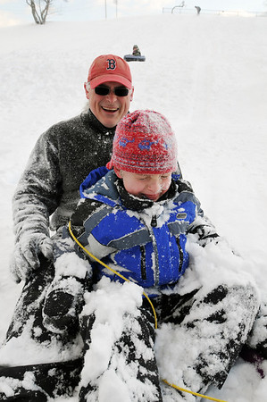 Salem: Dainis Kaulenas of Salem and his son Corey, 6, are covered with powder snow after sledding down a hill at Mack Park. photo by Mark Teiwes / Salem News