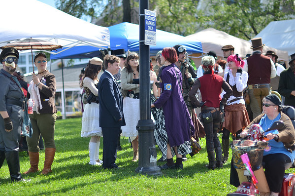 "Salem:  Jerry Bottari of Salem, right, passes by the ""Steampunk Invasion of Salem"" event on Pickering Wharf.   photo by Mark Teiwes / Salem News"
