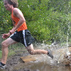 Topsfield:  Beverly's Nick Robinson splashes through a puddle on the . Bradley Palmer State Park cross country course.  photo by Mark Teiwes / Salem News