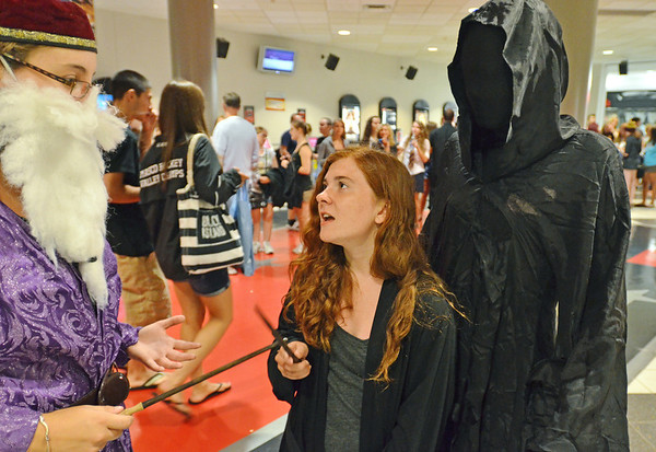 Danvers: Nicole Chaisson dressed as Professor Dumbledore , left,  Jessica Doherty as Ginny Weasley, and Sean Haggett as a Dementor, all from Marblehead, wait in line for one of 20 sold out midnight screenings of the final Harry Potter movie.   People began lining up a 5:00pm to get the first seats.  photo by Mark Teiwes / Salem News