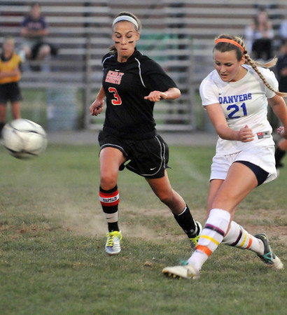 Danvers: Danvers player Kristin Yost, right, puts a shot on goal watched by North Andover's Olivia Boudreau. Yost scored the game's first goal off a corner kick. photo by Mark Teiwes / Salem News