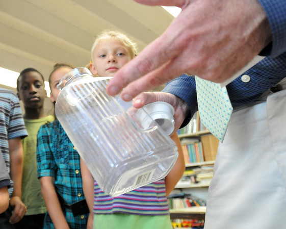 Salem: Greenhouse school director Dan Welch holds a jar money that was taken when the school was robbed.  The students had saved money to send to a Haitian school. photo by Mark Teiwes / Salem News