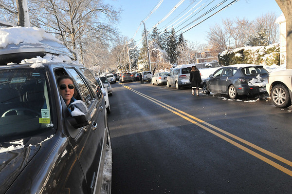 Marblehead: Meredith Davis, left, waits to pick up her daughter in fifth grade at Village School.  Other parents parked on both sides of Village Street.   She voiced concerns about the lack of shoveled sidewalks.  photo by Mark Teiwes  / Salem News