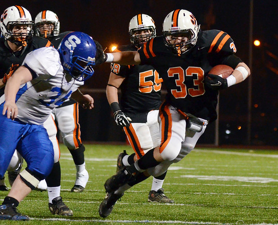 Lynn:  Beverly's Brendan Flaherty, right, stiff arms Scituate's Matt King.  Flaherty scored two touchdowns in the game. photo by Mark Teiwes / Salem News