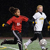 Peabody: Salem's Maria Rodriguez, left, carries the ball upfield followed by Bishop Fenwick's Kim Shinnick during last night's game in the rain. photo by Mark Teiwes / Salem News
