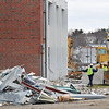 Beverly:   Next to a pile of collected metal, construction workers move plastic sheets continuing the demolition of the old Beverly High School.  photo by Mark Teiwes / Salem News