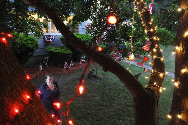 Peabody: Sharon Kokoras is seen through a decorated tree at her house in honor of her nephew Lt. Commander Gerald P. Flinn III.  She has continued to keep them up since Christmas as he serves in Iraq.  photo by Mark Teiwes / Salem News