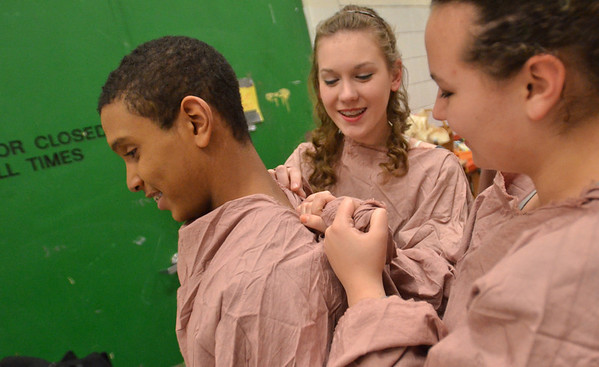 Salem: Kenny Tejeda, left, gets tied into his costume with help from Aletha Spang, and Alexis MacTalor, right.    photo by Mark Teiwes  / Salem News