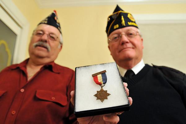 Salem: Roger Ledger, commander of the Salem Veterans Council, left, and Tom Moran, past commander of the Second Corps Cadets of VA for 101-102 Field Artillery hold a medal from World War I.   photo by Mark Teiwes / Salem News