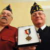 Salem: Roger Ledger, commander of the Salem Veterans Council, left, and Tom Moran, past commander of the Second Corps Cadets of VA for 101-102 Field Artillery hold a medal from World War I.   photo by Mark Teiwes / Salem News