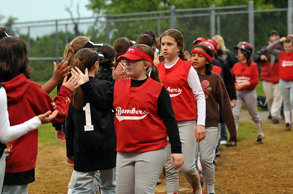 Salem: 10 year old Meghan Latham of the Bombers slaps hands with the Sea Dogs girls softball team after a game. photo by Mark Teiwes / Salem News