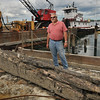 Salem: Phil Pelletier stands beside the keel from the USS New Hampshire, a sister ship of USS Constitution, built in 1816.  He dug it up while dredging at Dion Yacht Yard.  photo by Mark Teiwes / Salem News