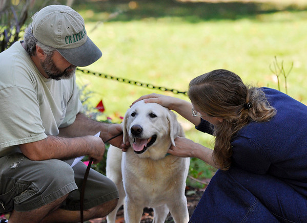 Danvers: Sid Sarantis of Danvers, left, kneels with 13-year-old Katie his yellow lab as she is blessed by Thea Keith-Lucas.