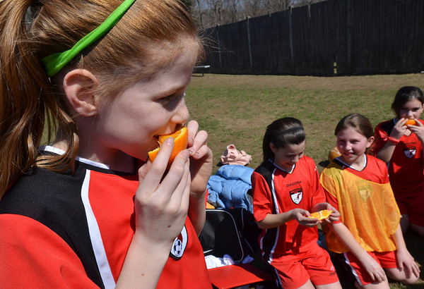 Middleton:  Brita Evans, U-10 girls travel soccer Middleton Flash player, enjoys an orange slice at half tiem   photo by Mark Teiwes / Salem News