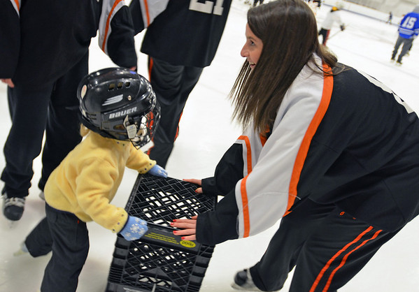 Gloucester: Clare Leathersich, Danvers/Beverly girls hockey captain skates with Morgan Linskey, 3, of Marblehead.  photo by Mark Teiwes  / Salem News