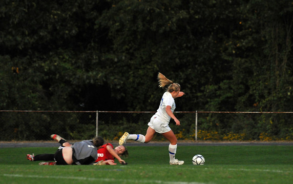 Danvers:  Danvers High School girls soccer player Corey Persson, right, leaves the Salem defense and goal on the ground on her way to the goal.  photo by Mark Teiwes / Salem News