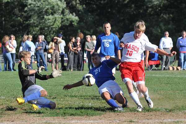 Topsfield: Masconomet's Nevin Clay, right, struggles to reach the ball challenged by Danvers defender Ethan Collins, and goal keeper Andrew Douglas, left.  photo by Mark Teiwes / Salem News