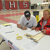 Salem: Jordon Day, left, of Lynn and Jody Power of North Reading, both Red Cross volunteer shelter managers, help set up a shelter at the Salem High School.  photo by Mark Teiwes / Salem News