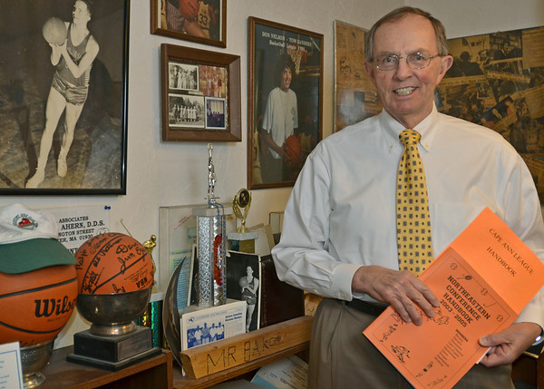 Marblehead: Dick Baker is retiring as the secretary treasure of Northeastern Conference and Cape Ann League for many years. Baker holds the leagues handbooks in his home office surrounded by some of his many awards .  photo by Mark Teiwes / Salem News