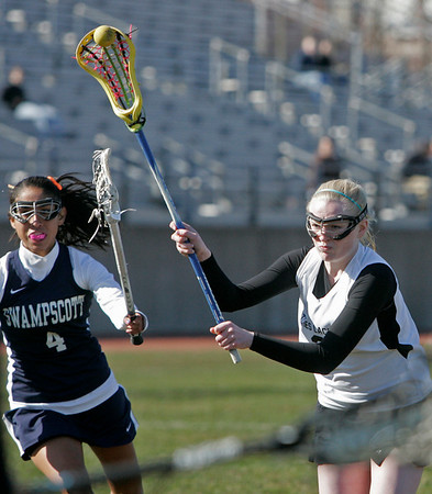 Salem: Salem lacrosse player Sophie Wyke sails past Swampscott's Gabby Wooten to score a goal.  photo by Mark Teiwes / Salem News