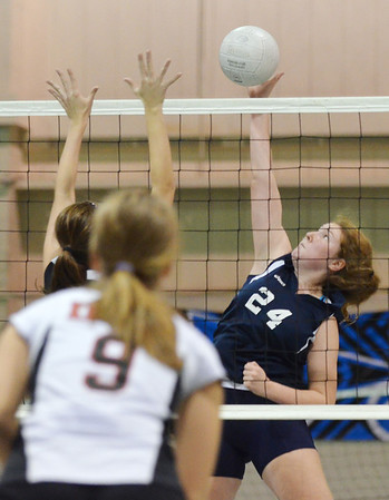 Peabody: Peabody's Caitlyn Thompson spikes the ball out of the reach of a North Andover block.  photo by Mark Teiwes / Salem News