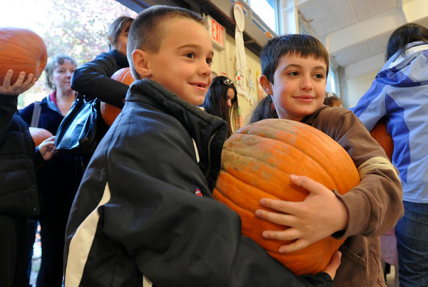 Middleton: 7-year-old Blake Buonopane, left, and Dominick Gecoya, 8, help each other carry a pumpkin to be carved.  They thought they had found the biggest.   photo by Mark Teiwes / Salem News