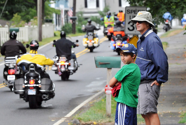 Wenham:  Oliver Wolcott III of Wenham and his son Oliver Wolcott IV watch as Nelson's Ride motorcyclists cruise through Wenham on Sunday afternoon.    photo by Mark Teiwes / Salem News