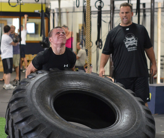 Danvers:   Bishop Fenwick quarterback Nick Bona lifts a 400lb tire watched by Pat Downey during a workout at Gridiron Training photo by Mark Teiwes /  Salem News