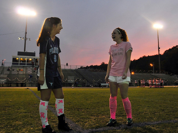 Danvers:   Peabody captain Emily Manoogian, left, and Danvers captain Becky Landers worked together to organize their teams to wear pink socks during a game to promote breast cancer awareness.  photo by Mark Teiwes / Salem News