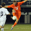 Beverly: Salem State defender Brandon LeBlanc jumps to clear the ball with a volley.  photo by Mark Teiwes / Salem News