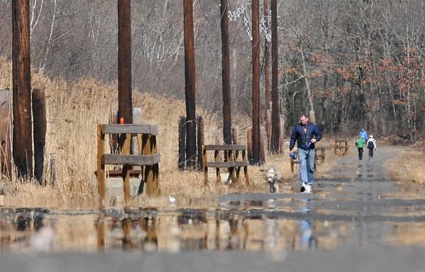 Peabody: Bill Plona walks on his day off with his dog at the Independence Greenway along the Ipswich River.  photo by Mark Teiwes / Salem News
