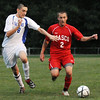 Danvers:  Masconomet captain Chad Burke, right, dribbles upfield covered by Danvers defender Drew Piazza.   Burke scored two goals in Masco's 5-1 win. photo by Mark Teiwes / Salem News