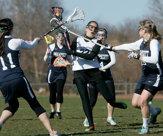 Salem: Salem lacrosse player Brianna Freeman, center, powers through Swampscott defenders to score a goal.   photo by Mark Teiwes / Salem News