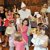 Topsfield:  Joyce Bergsten, center, a member of the Precilla Capen Herb Society, directs children to hold up their dolls after a reading of the Tale of Peter Rabbit during a tea party in the Gould Barn. She is wearing an outfit she has had for 30 years.  photo by Mark Teiwes / Salem News