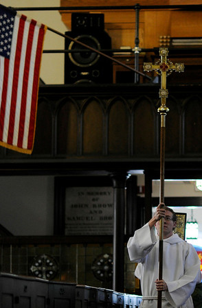 Salem:  Ben Whaley carries a cross during the processional of mass at San Pedro Episcopal Church.  Mr. Whaley is part of a group going to Arizona with Promise Arizona to register Hispanic voters.  photo by Mark Teiwes / Salem News
