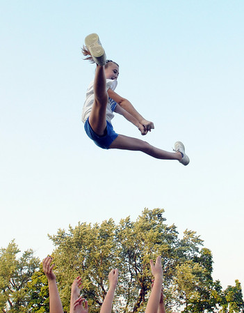 Danvers: Seventh grader Rebecca Redfield soars through the air on a basket toss during Danvers cheering squad practice.  photo by Mark Teiwes / Salem News