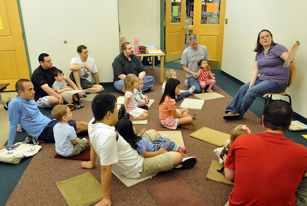 Hamilton: Children's room librarian Season Bos, right reads a story during the Dad's and Donuts program at the Hamilton-Wenham Public Library.  photo by Mark Teiwes / Salem News